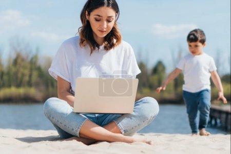 selektive Fokussierung von Freelancer mit Laptop, während sie auf Sand in der Nähe von niedlichen Sohn sitzen