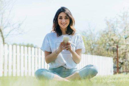 enfoque selectivo de la mujer alegre sentado en la hierba verde y la celebración de teléfono inteligente