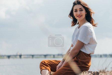 selective focus of cheerful woman looking at camera near lake