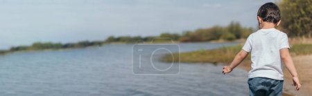 Photo for Website header of boy standing and gesturing near pond - Royalty Free Image