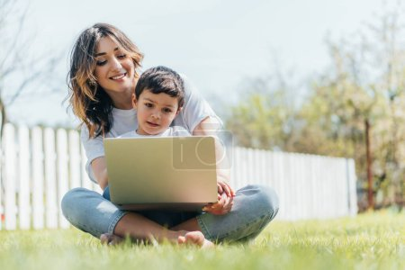 selective focus of happy mother and son using laptop while sitting on grass