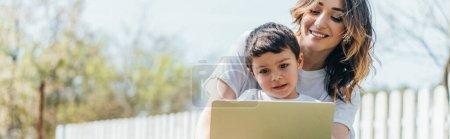 Photo pour Concept horizontal de mère heureuse et son fils en utilisant un ordinateur portable à l'extérieur - image libre de droit