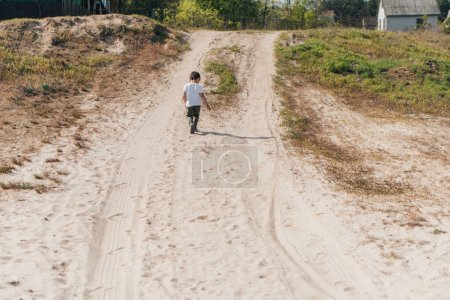 back view of kid walking on sand outside