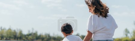 Photo for Horizontal crop of beautiful mother looking at son while sitting outside - Royalty Free Image