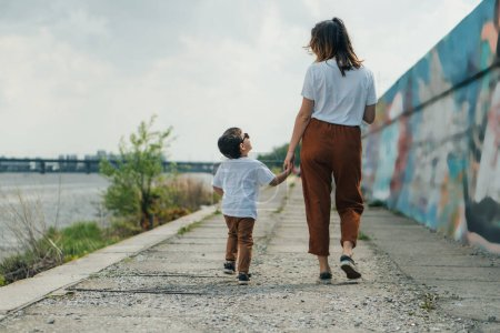vista trasera de la madre cogida de la mano con lindo hijo fuera