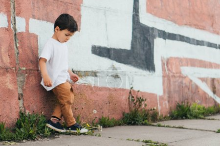 Photo for Cute boy looking down while standing near painted wall - Royalty Free Image