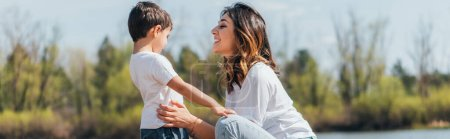 Photo for Panoramic shot of happy mother sitting and touching son - Royalty Free Image