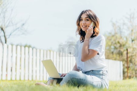 enfoque selectivo de freelancer atractivo hablando en el teléfono inteligente cerca de la computadora portátil y sentado en la hierba