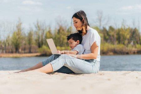Selektiver Fokus von Mutter und Sohn, die auf Sand sitzen und Laptop benutzen