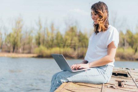 Photo pour Heureux pigiste souriant et en utilisant un ordinateur portable près de la rivière - image libre de droit