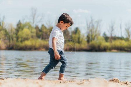 Photo pour Vue latérale du garçon pieds nus marchant sur du sable mouillé près de l'étang - image libre de droit