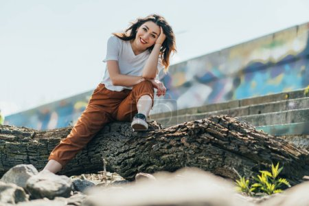 selective focus of cheerful woman sitting on tree trunk