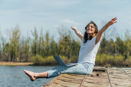 cheerful woman with outstretched hands sitting with laptop near lake