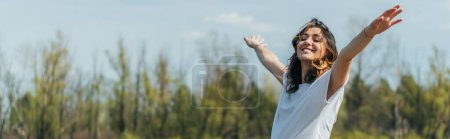 Photo for Horizontal crop of cheerful woman with outstretched hands smiling outside - Royalty Free Image