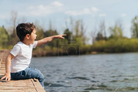Photo for Profile of emotional boy pointing with finger while sitting near river - Royalty Free Image