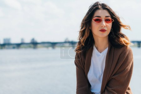 Photo for Trendy woman in stylish sunglasses looking at camera near lake - Royalty Free Image