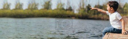 Photo pour En-tête de site Web de garçon émotionnel pointant du doigt tout en étant assis près de la rivière - image libre de droit