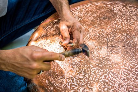 Senior craftsman,tinsmith,working with hammer during hand stamping or engraving decoration pattern on metal plate.Copper master, hands detail of craftsman at work.
