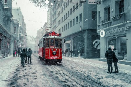 Winter view of nostalgic red Tram and people in daily life while snowing at popular Istiklal Street of Beyoglu,Istanbul,Turkey.07 January 2017