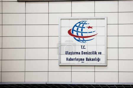 Logo of Turkish Republic maritime transport and Communication Ministry on a white stone wall.