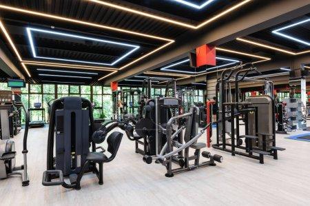 Photo pour Intérieur moderne et élégant salle de gym avec équipement, certains mouvements flous personnes méconnaissables - image libre de droit