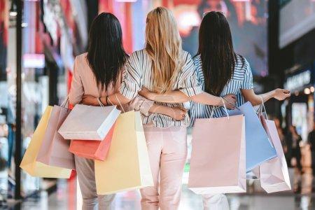 Photo pour Trois jolies jeunes filles font du shopping avec des sacs à provisions dans un centre commercial moderne . - image libre de droit