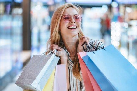 Photo pour Attrayant jeune femme heureuse fait du shopping avec des sacs à provisions dans un centre commercial moderne . - image libre de droit