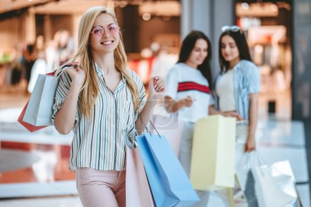 Photo for Three attractive young girls are doing shopping with shopping bags in modern mall. - Royalty Free Image