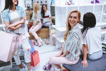 Photo for Three attractive young girls are doing shopping with shopping bags in shoes store in in modern mall. - Royalty Free Image