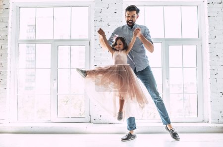 Photo for I love you, dad! Handsome young man is dancing at home with his little cute girl. Happy Father's Day! - Royalty Free Image