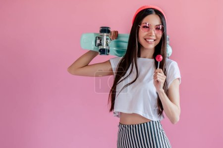 Young asian teenage girl on pink background. Stylish girl with lollipop and skateboard isolated.