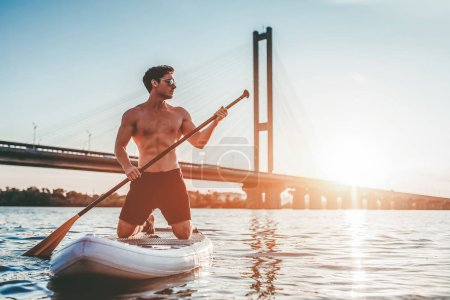 Man on stand up paddle board. Having fun on SUP board during sunset. Active lifestyle.