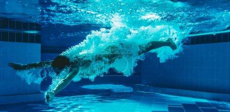 Photo pour L'homme saute dans la piscine. L'homme nage sous l'eau dans la piscine . - image libre de droit