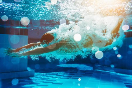 Photo for Man is jumping into the swimming pool. Man is swimming under water in swimming pool. - Royalty Free Image