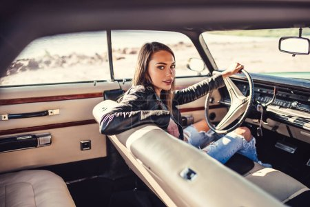 Photo for Attractive young woman is sitting in green retro car on the beach. Vintage classic car. - Royalty Free Image