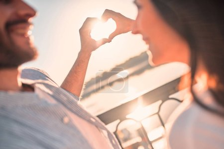 Photo for Love is in the air! Cropped image of cute romantic couple spending time together in the city. Handsome bearded man and attractive young woman are in love. Hugging, kissing and having fun during the sunset. - Royalty Free Image