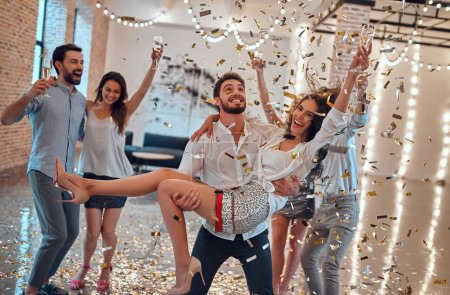 Photo for Let the party begin! Group of young people having fun together. Dancing in big light room with champagne and confetti falling. Celebrating holiday in big company of close friends. - Royalty Free Image