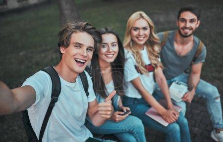 Photo pour Des groupes de jeunes étudient ensemble à l'université. Les étudiants en plein air faisant selfie . - image libre de droit