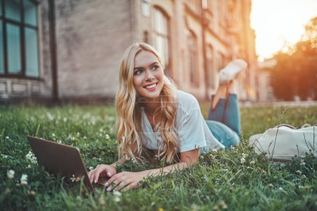 Attractive young woman is studying near university. Female student is lying on grass outdoors with laptop.