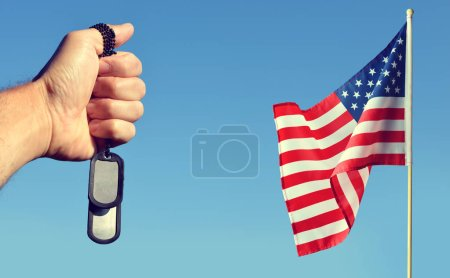 American flag and hand with soldiers tags on blue sky. Veterans or Memorial Day concept.