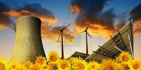 Foto de Paneles de energía solar con turbinas eólicas y torre de refrigeración de la central nuclear al atardecer . - Imagen libre de derechos