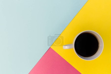 Coffee cup on bright minimal yellow, pink and blue background