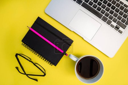 Laptop with eyeglasses, coffee cup, notebook and pencil on bright yellow background