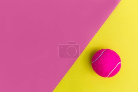 Photo for Pink tennis ball on bright yellow and pink background - Royalty Free Image