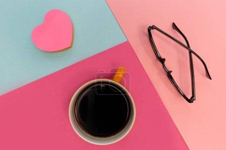 Photo pour Tasse à café, lunettes et coeur d'amour sur fond rose vif et bleu - image libre de droit