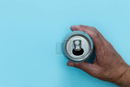 Photo for Hand holding drinks can on bright blue background - Royalty Free Image