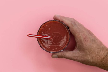 Male hand holding red strawberry smoothie drink on pink background