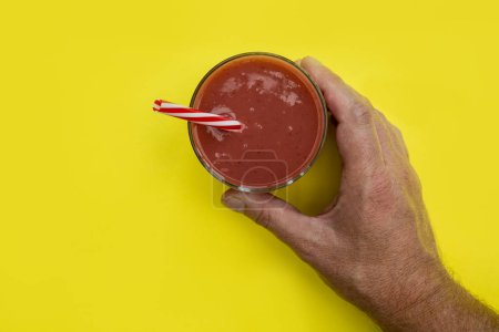 Male hand holding red strawberry smoothie drink on yellow background
