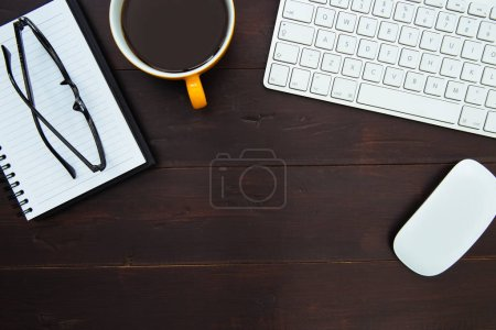 Computer keyboard, coffee cup, eyeglasses and mouse on wood office desk workspace