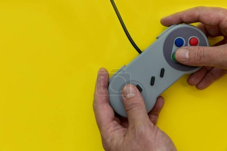 Man playing video game with controller on yellow background